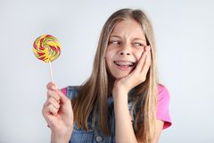 Young girl with lollipop. On grey background royalty free stock photography
