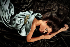 Young girl with long black hair. Lying poses no iridescent fabric Royalty Free Stock Photography