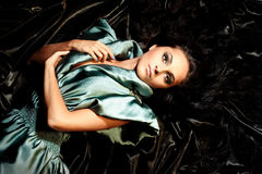 Young girl with long black hair. Lying poses no iridescent fabric Royalty Free Stock Image