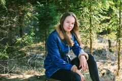 A young girl with long blond hair and a denim jacket sits on a log in a green coniferous forest on a warm sunny spring day.  stock photos