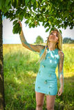 Young girl with long blond hair. E picks cherry from a fruit tree and smiles Stock Photography