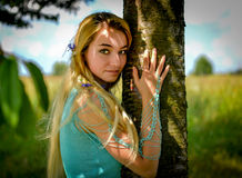Young girl with long blond hair. Hugging tree trunk Royalty Free Stock Photo