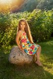 Young girl with long blond hair sits on a stone in the rays of a bright sun Royalty Free Stock Images