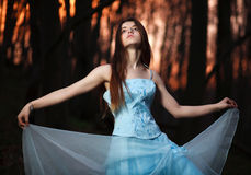 Young girl in a long blue dress dancing in the dark forest Stock Image