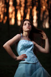 Young girl in a long blue dress posing in a dark forest Royalty Free Stock Photos