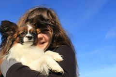 A young girl with long brown hair holds a little hairy dog. She is happy and smiles and the dog looks like smart. They are  on the summer blue sky Royalty Free Stock Images