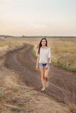 Young girl with long brown hair walking along the road in field Royalty Free Stock Photography