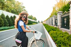 Young girl with long curly hair in blue sunglasses is going by bicycle on road. She wears long skirt, jerkin, hat. Sh.  stock photo
