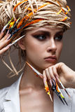 A young girl with long decorated nails and bright creative makeup. Beautiful model with a straw hat on her head. Beautiful manicur Stock Images
