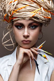 A young girl with long decorated nails and bright creative makeup. Beautiful model with a straw hat on her head. Beautiful manicur Stock Photography