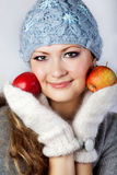 Young girl with a long fair hair. Is dressed in a woollen cap, a scarf, mittens. She holds hands two apples. She smiles and looks in the chamber Stock Photography