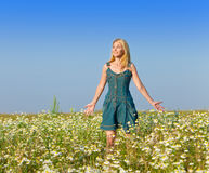 The young girl with a long fair hair in a blue dress costs in the field of camomiles against the blue sky Royalty Free Stock Photography
