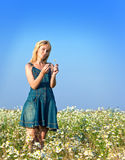 The young girl with a long fair hair in costs in the field of camomiles Stock Photo
