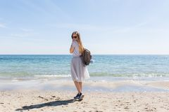 Young girl with long hair and bag on back is looking to the camera near sea. She wears lush gray skirt and gray T-shir.  royalty free stock photo