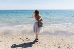 Young girl with long hair and bag on back is looking to the sea. She wears lush gray skirt and gray T-shirt wit.  royalty free stock image