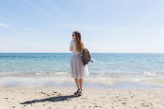 Young girl with long hair and bag on back is standing near sea. She wears lush gray skirt and gray T-shirt with sneaker.  stock image