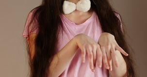 Young girl with long hair holds her hands in front of her like hare and sorts her fingers. On hair are fixed white-pink ears. Of Easter Bunny. Easter eve stock video