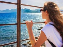 Young girl with long hair looks at the blue sea through the bars stock photo