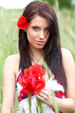Young girl with long hair in poppies field Stock Photo