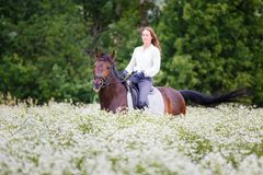 Young girl with long hair riding horse on field Stock Images
