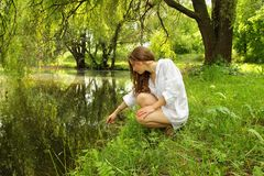 Young girl with long hair sitting near the lake in the shade Royalty Free Stock Photography