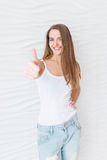 Young girl with long hair smiling and showing gesture `Cool`, shows evaluation of cosmetic product, recommends beauty salon or res Royalty Free Stock Image