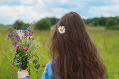 Young girl with long hair standing back to us with wildflowers. Concept of seasons, environment, natural beauty, summer. Young girl with long hair standing back Stock Photography