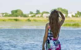 A young girl with long hair turned her back and stares into the distance on the river bank. Stock Images