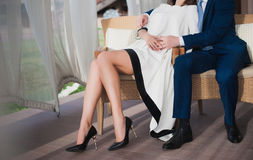 A young girl with long legs sitting and embraces the man Stock Image