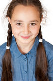 A young girl with long pigtails. Looks and smiles stock photos