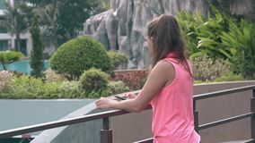 Young girl with long ponytail stands by balcony metal fence. Trendy tanned young girl with long ponytail stands by balcony metal fence searching photos close stock footage