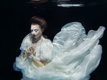 Young girl in long white dress underwater Royalty Free Stock Photo