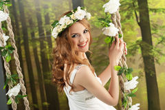 Young girl in a long white dress, with a wreath on a swing in the studio.  Stock Images