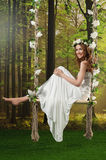 Young girl in a long white dress, with a wreath on a swing in the studio.  Royalty Free Stock Image