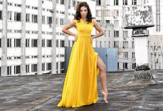 Young girl in a long yellow dress on the roof of a building in the city. Sexy Girl in a long yellow dress, barefoot on the roof of a building in the city Stock Photos