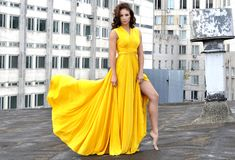 Young girl in a long yellow dress on the roof of a building in the city. Sexy girl in a long yellow dress, on the roof of a city building Royalty Free Stock Photos