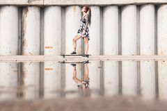 Young girl with a longboard on the background of concrete structure royalty free stock image