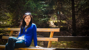 Young girl look aside when sitting on bench Royalty Free Stock Photos