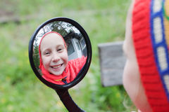 The young girl. Look in the funhouse mirror on the nature royalty free stock images