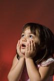 Young girl looking in awe. Young girl holding her hands in the air looking in awe Stock Image