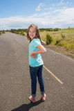 Young girl looking back while traveling on quiet country road Royalty Free Stock Photography