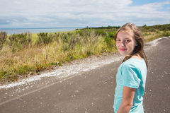 Young girl looking back while traveling on quiet country road Stock Image