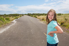 Young girl looking back while traveling on quiet country road Stock Photography