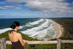 Young girl is looking at beautiful coastline. Young girl is looking at beutifull coastline and waves hitting the beach. Green landscape at the distance. Byron stock images