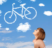 Young girl looking at bicycle clouds on blue sky Royalty Free Stock Images