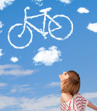 Young girl looking at bicycle clouds on blue sky Stock Images
