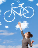 Young girl looking at bicycle clouds on blue sky Royalty Free Stock Photos