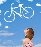 Young girl looking at bicycle clouds on blue sky Stock Photo