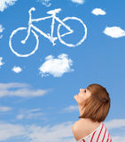 Young girl looking at bicycle clouds on blue sky Royalty Free Stock Photography