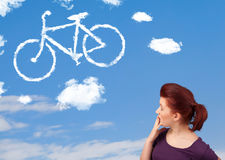 Young girl looking at bicycle clouds on blue sky Royalty Free Stock Photo